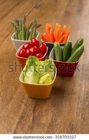 Fresh vegetables in colourful bowls on a wooden table. Healthy party snacks. Asparagus, cucumbers, carrots, lettuce leaves and cherry tomatoes.  - stock photo