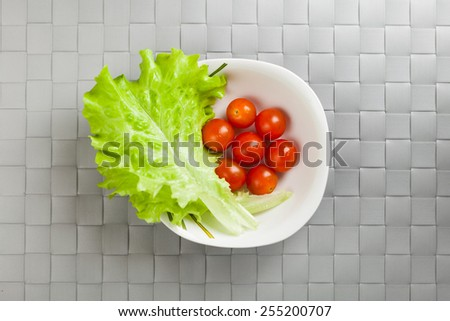 fresh vegetables on plate, grey place mat background - stock photo