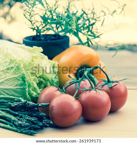 Fresh vegetables on wooden cutting board, vintage style, selective focus, shallow dof. - stock photo
