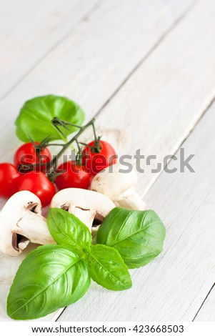 Fresh vegetables - sliced champignons, cherry tomatoes and basil - on wooden background with copyspace - stock photo
