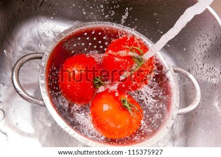 Fresh vegetables under water stream in colander - stock photo