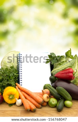 Fresh vegetables with notes on wooden table on green background  - stock photo