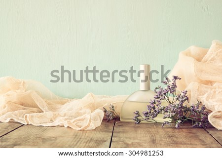 fresh vintage perfume bottle next to aromatic flowers on wooden table. retro filtered image  - stock photo