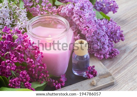 fresh violet lilac flowers with burning candle - stock photo