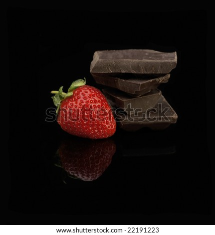 fresh vivid colored strawberry and broken chocolate bar over black background - stock photo