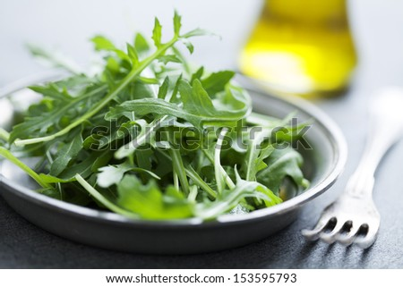 fresh, washed baby rocket on a wooden chopping board - stock photo