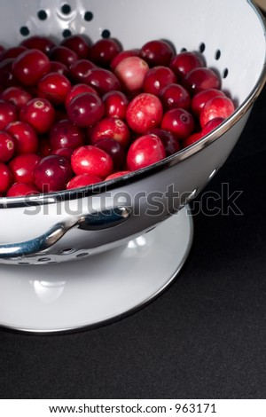 fresh, washed cranberries in white colander - stock photo