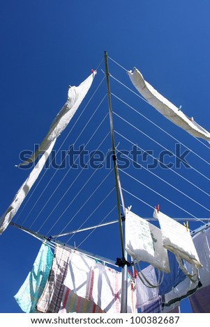 fresh washed laundry on rotary clothes dryer - stock photo