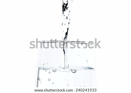Fresh water pouring into a clear glass - stock photo