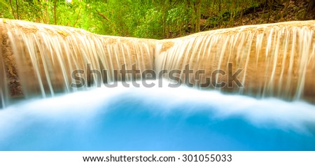 Fresh water river flows and falls from waterfall cascade. Smooth and silky stream nature background - stock photo