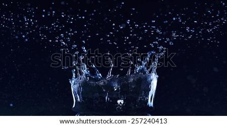 Fresh water splash like a crown on dark background - stock photo