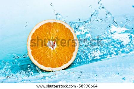 fresh water splash on orange - stock photo