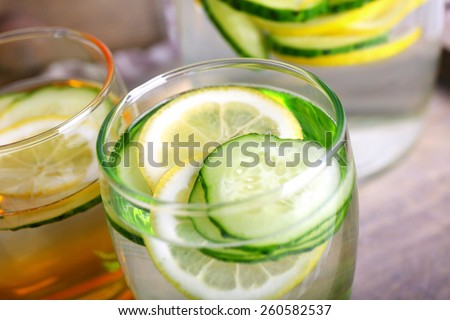 Fresh water with lemon and cucumber in glassware in wooden tray, closeup - stock photo