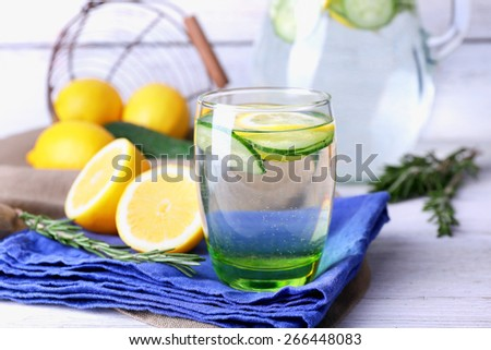 Fresh water with lemon and cucumber in glassware on napkin on wooden table, closeup - stock photo