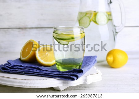 Fresh water with lemon and cucumber in glassware on wooden background - stock photo