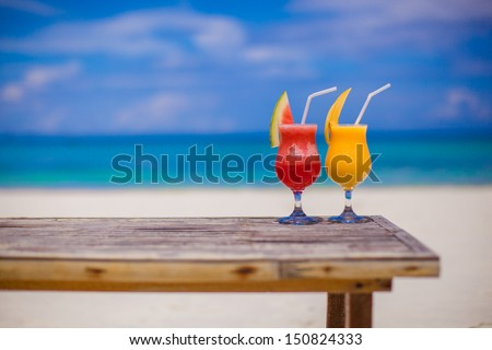 Fresh watermelon and mango cocktails on woodem table background of stunning turquoise sea - stock photo