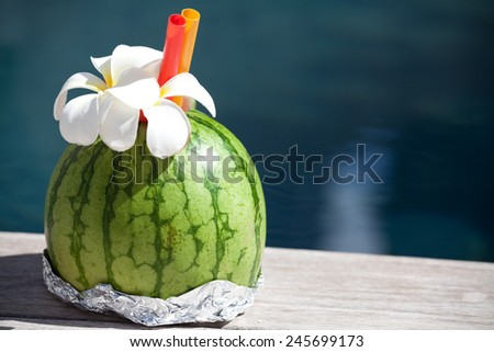 Fresh watermelon cocktail at the edge of the swimming pool. - Luxury Vacation Concept - stock photo