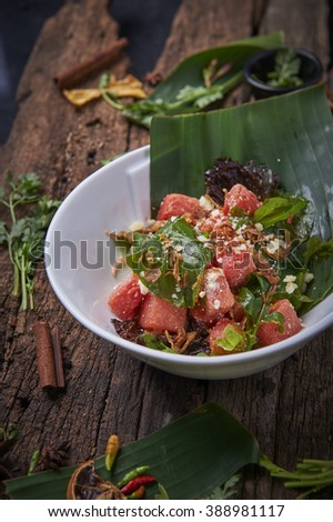 Fresh Watermelon Salad with Mint and Feta cheese on Banana leaf served in a white bowl on mood background - stock photo