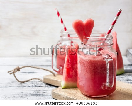 fresh watermelon smoothie in a mason jar, slices of watermelon in the form of heart on the wooden background - stock photo