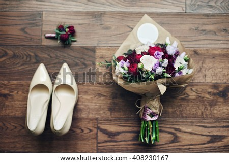Fresh wedding bouquet, white shoes, boutonniere on wooden background closeup - stock photo