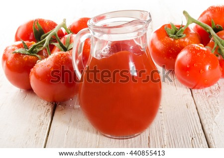 fresh wet tomato on white wood and tomato juice in a glass jug - stock photo