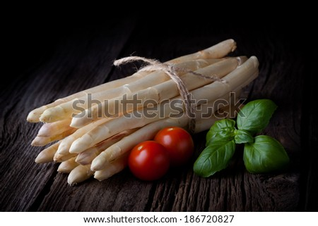 Fresh white asparagus bunch, tomatoes and basil composition. Spring vegetables tied with a string taken on white background. - stock photo