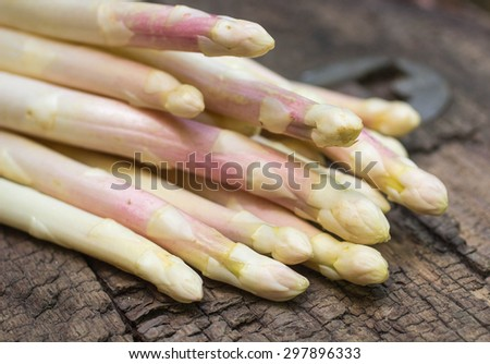 Fresh white asparagus on an old wooden table. Shallow depth of field - stock photo