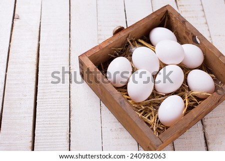 Fresh white eggs in box on white wooden painted planks. Selective focus. - stock photo