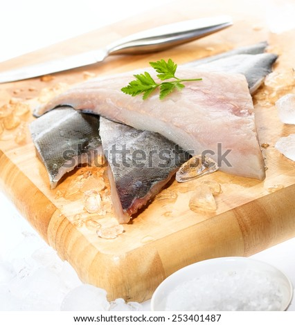 Fresh white fish fillets displayed on chopping board with crushed ice, knife, cracked rock salt and parsley garnish  - stock photo
