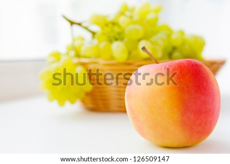 Fresh white grapes in basket on white windowsill - stock photo