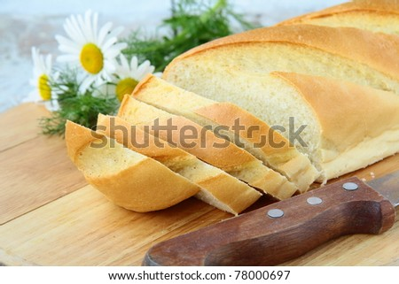 fresh white loaf of bread with a knife and daisies, rustic style - stock photo