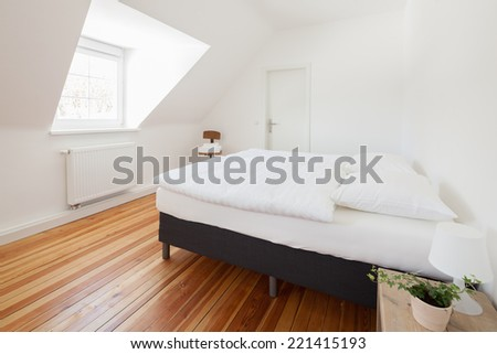 Fresh white modern bedroom interior with a dormer window, wooden parquet floor and double bed - stock photo