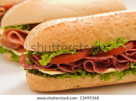 Fresh whole wheat salami and cheese sandwich with lettuce and tomatoes  in the foreground and a ham sandwich in the background - stock photo