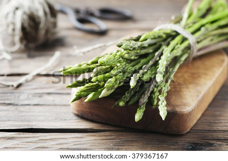 Fresh wild asparagus on the wooden table, selective focus - stock photo