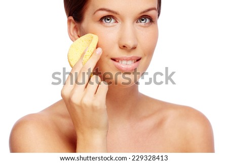 Fresh woman with sponge cleaning her face - stock photo