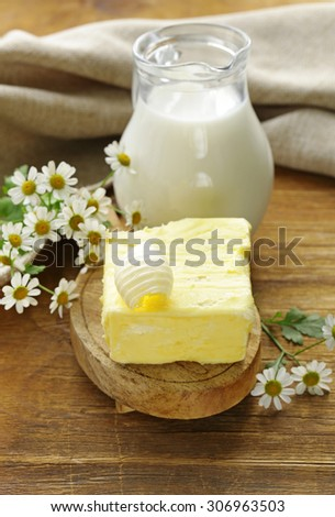fresh yellow butter with a jug of milk, rustic still life - stock photo
