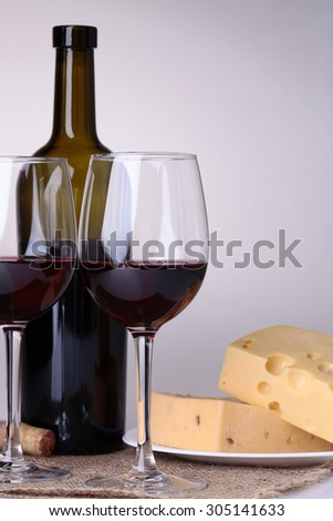 Fresh yellow delicious delicatessen dairy product of cheese slices on plate near crystal glass goblets and bottle with red wine standing on white table top on grey background, vertical picture - stock photo