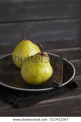 fresh yellow pears on a brown plate on a dark wooden surface - stock photo