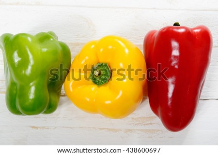 fresh yellow, red and green bell peppers on white wooden table - stock photo