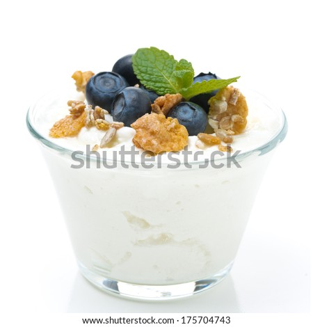 fresh yogurt  with muesli and blueberries in a glass, close-up, isolated on white - stock photo