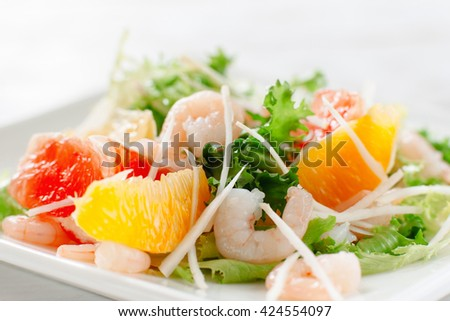 Fresh yummy shrimp salad with oranges and grapefruit  and cheese on the white dish. Close up. Top view of seafood salad with shrimp - stock photo