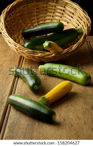 Fresh zucchini - green and yellow courgette, wicker basket, rustic table, dark background - stock photo