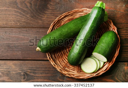 Fresh zucchini on wicker mat on wooden background - stock photo