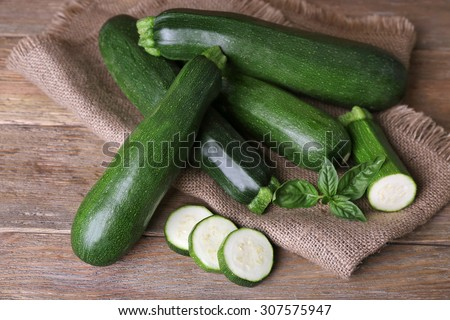 Fresh zucchini with basil on wooden table close up - stock photo