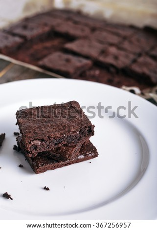 Freshly backed chocolate brownie stack on a white plate. With a pan of extra brownies on back on the dark, old and vintage wood background - stock photo