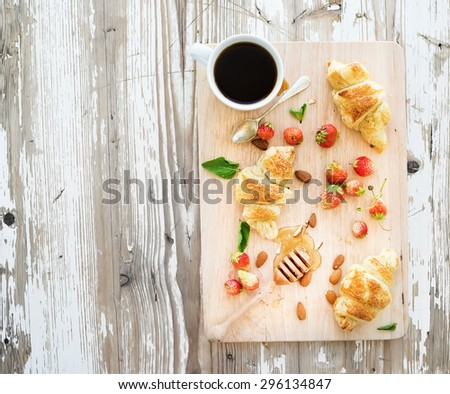 Freshly baked almond croissants with garden strawberries and honey on serving board over white rustic wood backdrop, top view, copy space - stock photo