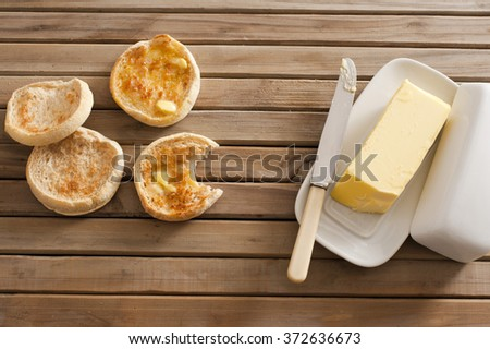 Freshly baked and toasted tasty crumpets, one bitten into, on a wooden table with a pat of butter on a plate, overhead view - stock photo