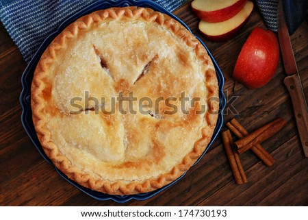 Freshly baked apple pie with cinnamon sticks and vintage knife on rustic, dark wood background.  Low key still life with directional, natural lighting for effect. - stock photo