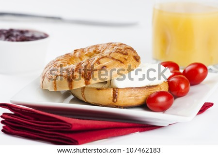 freshly baked bagel cut in half with cheese on top and cream cheese inside served on square plate with red napkin under. Glass of orange juice, cup of berry preserve/jam and small red cherry tomatoes. - stock photo