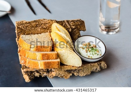 Freshly baked bread and cheese dip on tree bark, tasty starter, decorative food background on gray and blue table with glass of water. - stock photo